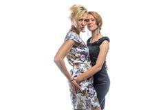 Retrato isolado de duas irmãs que estão no branco Imagem de Stock