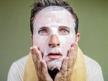 Retrato isolado estilo de vida do fundo do homem estranho e engraçado novo em casa que tenta usando a limpeza facial da máscara d foto de stock royalty free
