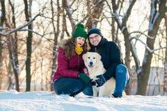 Retrato joven de los pares con el perro en invierno Fotos de archivo libres de regalías
