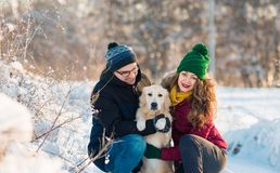 Retrato joven de los pares con el perro en invierno Imagen de archivo