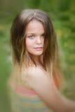 Retrato joven del adolescente con el fondo verde natural del seto Fotografía de archivo