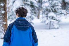 Retrato joven del adolescente masculino que camina en el bosque nevoso f del invierno imagen de archivo libre de regalías