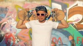 Retrato joven del patinador del adolescente La persona con un monopatín se coloca cerca de una pared en una calle almacen de video