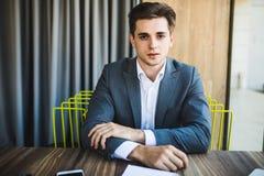 Retrato joven feliz del hombre de negocios en la oficina moderna brillante interior Fotos de archivo libres de regalías