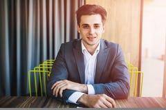Retrato joven feliz del hombre de negocios en la oficina moderna brillante interior Fotografía de archivo libre de regalías