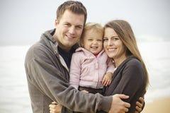 Retrato joven hermoso de la familia en la playa Imagenes de archivo