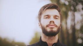 retrato 4K de un hombre europeo sonriente confiado Ciérrese encima de tiro del ángulo bajo Hombre hermoso barbudo que anticipa po almacen de video