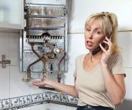 Retrato la mujer joven que el ama de casa llama en un taller sobre la reparación de los calentadores de agua del gas Fotos de archivo