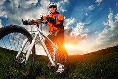 Retrato largo do ângulo contra o céu azul do ciclista do motociclista da montanha Imagens de Stock Royalty Free