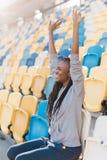 Retrato lateral al aire libre del adolescente afroamericano hermoso que anima para el equipo mientras que se sienta en los asient Fotografía de archivo