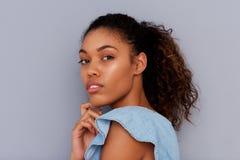 Retrato lateral da mulher afro-americano nova bonita contra a parede cinzenta fotos de stock