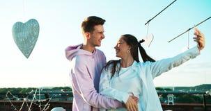 Retrato lateral de los pares atractivos jovenes de los amantes que ríen y que toman selfies vía el teléfono móvil en el tejado almacen de metraje de vídeo