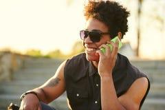 Retrato lateral de un hombre joven feliz que usa el teléfono móvil afuera Imagen de archivo libre de regalías