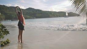 Retrato lateral de una mujer joven que respira el aire fresco, colocándose en una playa