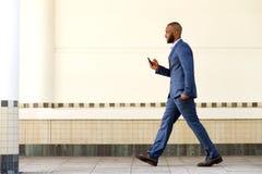 Retrato lateral del hombre de negocios africano joven que camina con el teléfono móvil Fotos de archivo libres de regalías