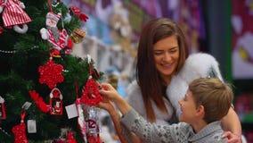 Retrato lateral del primer de la madre alegre y de su hijo observando los decoraions preciosos en el árbol de navidad en almacen de metraje de vídeo