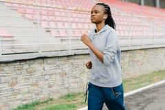 Retrato lateral del primer de la mujer afroamericana seria que activa a lo largo del estadio mientras que escucha la música en Fotografía de archivo
