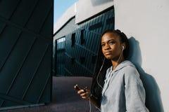 Retrato lateral del primer del adolescente afroamericano encantador que escucha la música en los auriculares mientras que se incl Foto de archivo libre de regalías