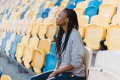 Retrato lateral del primer del adolescente afroamericano serio hermoso Ella está observando el partido mientras que se sienta en Fotografía de archivo libre de regalías