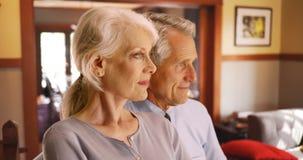 Retrato lateral dos pares superiores que sentam-se em casa olhando para fora a janela fotos de stock royalty free