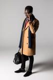 Retrato lateral integral del hombre de negocios africano joven usando el teléfono móvil aislado Fotografía de archivo libre de regalías