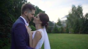 Retrato lateral sensível dos pares adoráveis de recém-casados no amante que abraça maciamente no jardim vídeos de arquivo