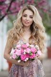 Retrato lindo de uma menina loura em um vestido cor-de-rosa 'sexy' da noite com um ramalhete de rosas bonitas imagens de stock