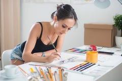 Retrato lindo joven de la imagen de la acuarela de la pintura de la mujer de un artista en el lugar de trabajo Fotografía de archivo
