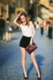 Retrato lleno de la moda de la calle del cuerpo de una mujer confiada hermosa joven que presenta en el fondo urbano Modele la mir Fotografía de archivo libre de regalías