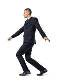 Retrato lleno del crecimiento de la cuerda tirante que camina del hombre de negocios aislada en el fondo blanco imagenes de archivo