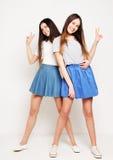 Retrato lleno del cuerpo de dos muchachas felices sobre el fondo blanco Imágenes de archivo libres de regalías