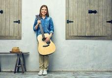 Retrato lleno del cuerpo de la mujer joven con la guitarra Imagen de archivo libre de regalías