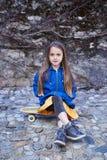 Retrato lleno del cuerpo de la niña positiva que se sienta en el monopatín Fotografía de archivo