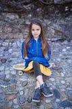 Retrato lleno del cuerpo de la niña positiva que se sienta en el monopatín Foto de archivo