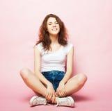 Retrato lleno del cuerpo de un modelo de moda femenino que se sienta en fondo rosado Foto de archivo