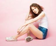 Retrato lleno del cuerpo de un modelo de moda femenino que se sienta en fondo rosado Imagen de archivo