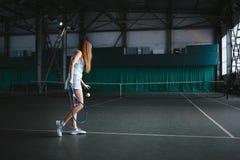Retrato lleno del cuerpo del jugador de tenis de la chica joven en la acción en un campo de tenis interior Foto de archivo