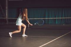 Retrato lleno del cuerpo del jugador de tenis de la chica joven en la acción en un campo de tenis interior Foto de archivo libre de regalías