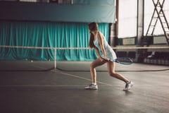 Retrato lleno del cuerpo del jugador de tenis de la chica joven en la acción en un campo de tenis interior Fotografía de archivo libre de regalías