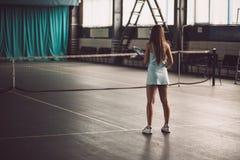 Retrato lleno del cuerpo del jugador de tenis de la chica joven en la acción en un campo de tenis interior Imagenes de archivo
