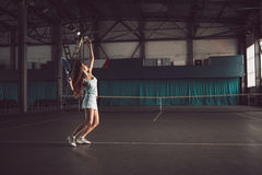 Retrato lleno del cuerpo del jugador de tenis de la chica joven en la acción en un campo de tenis interior Imagen de archivo