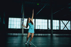 Retrato lleno del cuerpo del jugador de tenis de la chica joven en la acción en un campo de tenis interior Imagen de archivo libre de regalías