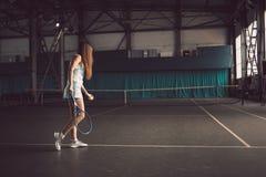 Retrato lleno del cuerpo del jugador de tenis de la chica joven en la acción en un campo de tenis interior Fotos de archivo libres de regalías
