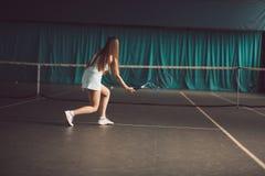 Retrato lleno del cuerpo del jugador de tenis de la chica joven en la acción en un campo de tenis interior Imágenes de archivo libres de regalías