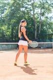 Retrato lleno del cuerpo del jugador de tenis rubio sonriente de la mujer en la acción en un campo de tenis al aire libre Imagen de archivo libre de regalías