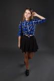 Retrato lleno-lenght de una muchacha en una camisa de tela escocesa y una falda negra Imagenes de archivo