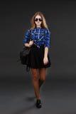 Retrato lleno-lenght de una muchacha en una camisa de tela escocesa y una falda negra Imagen de archivo libre de regalías