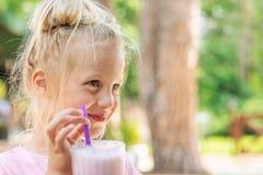 Retrato louro caucasiano da menina da criança em idade pré-escolar bonito adorável que sorve o coctail saboroso fresco do milk sh fotografia de stock