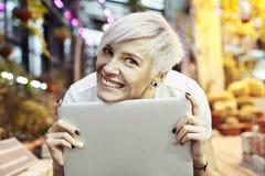 Retrato louro do close-up do cabelo curto da mulher bonita do moderno que sorri e que guarda o laptop Dia ensolarado em um parque Fotografia de Stock