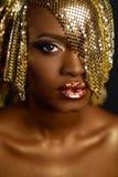 Retrato mágico hermoso de la mujer Maquillaje de oro Cara afroamericana modelo de la muchacha con la piel, los labios, el maquill Imagen de archivo libre de regalías